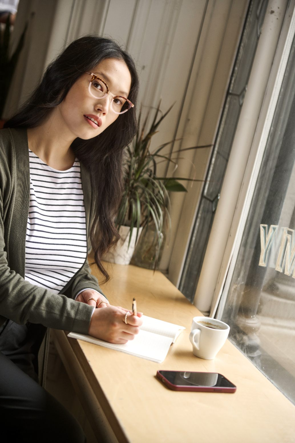 Woman sitting at a coffee writing on a notebook